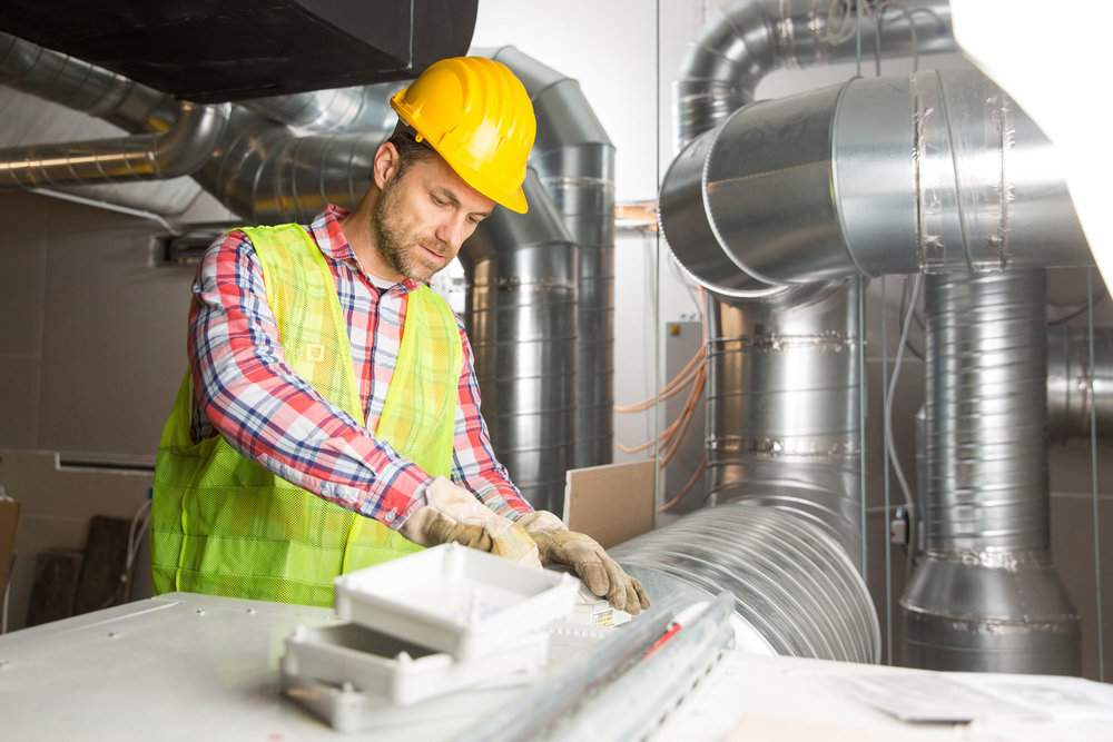 Use mobile HVAC forms to improve your customer service. (Image: Man in hard hat completes HVAC project)
