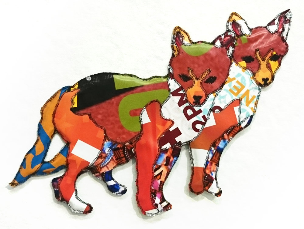 "Rachel Mello ,  Fox Pup Twins , recycled vinyl advertising banners, recycled coroplast, thread, 15 1/2"" x 19 1/2"", $200.  100% of the sale of this piece will be donated to  Arlington Public Arts ."