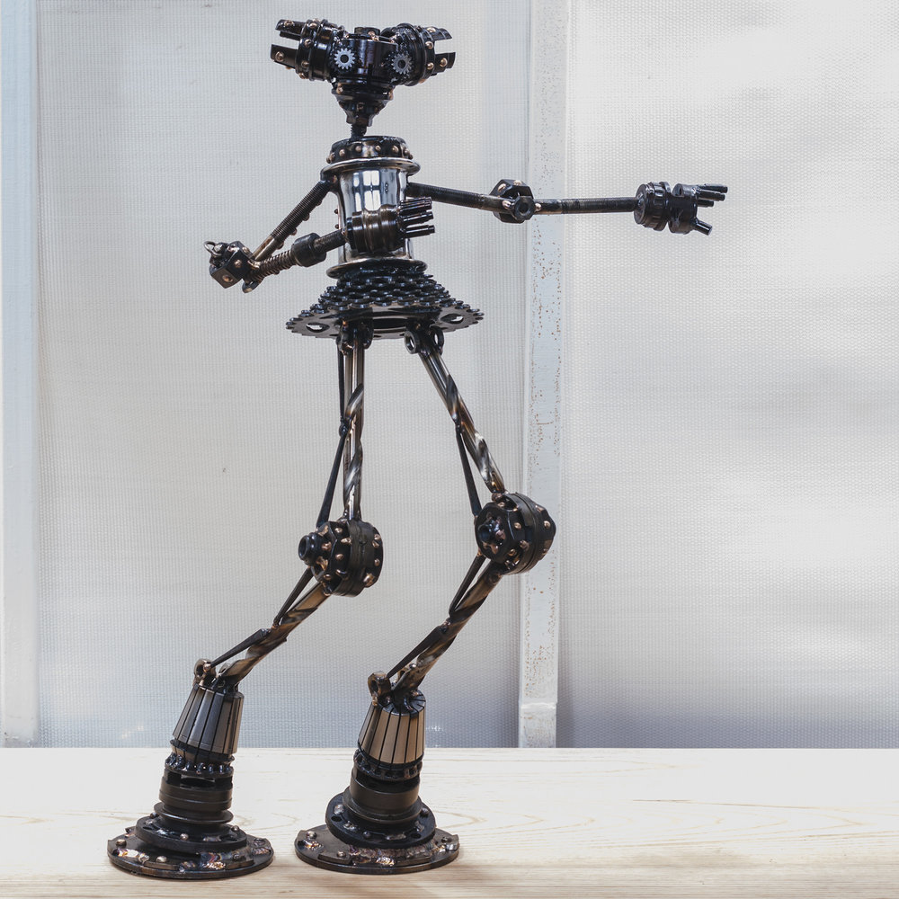 "Skunk ,  Gloria #M295 , Mercury class astrobot: bicycle parts, blades, washers, collets, pipe flanges, nuts, drill bits, nails, bolts, copper, bronze, stainless steel, 21"" x 14"" x 7"", $600"