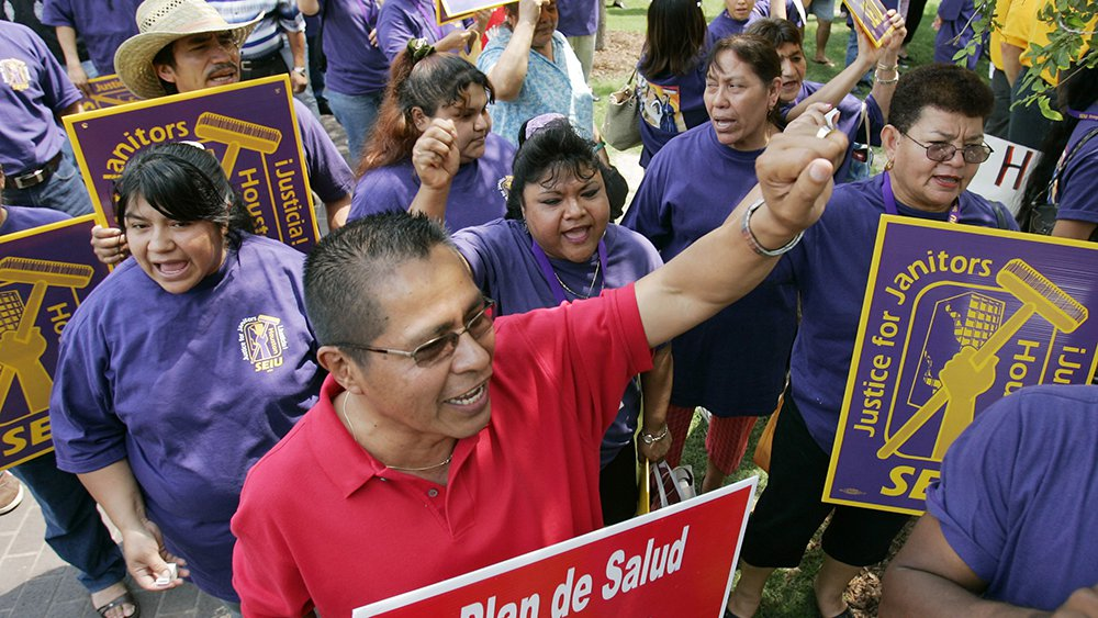 Janitors and their supporters chant during a protest on June 15, 2006, in downtown Houston. A jury later found that the janitors' union, the Service Employees International Union, used illegal tactics to force Professional Janitorial Service to unionize. (AP)
