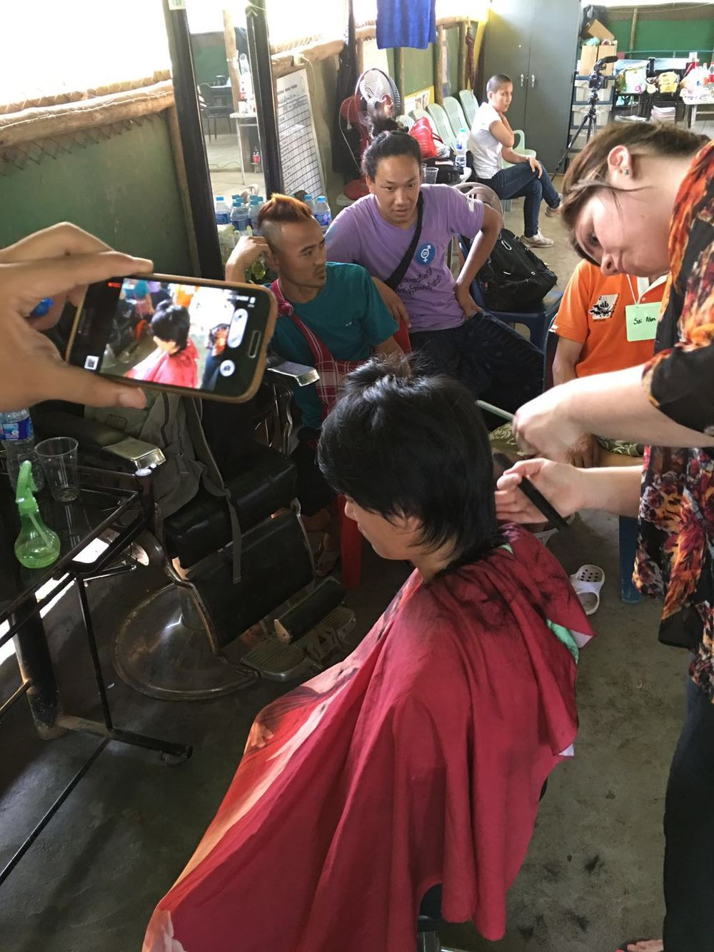 Natalie from HAUS South Minneapolis creates a modern men's haircut as a student documents the process on a smart phone.