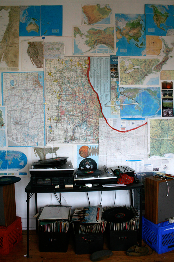 wall with maps of chicago and world and record player with boxes of records