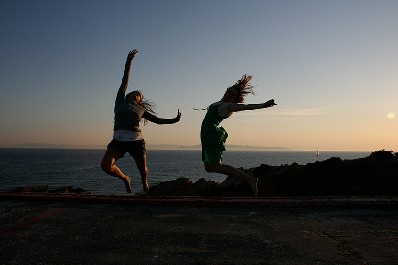 sisters jumping at sunset by the sea