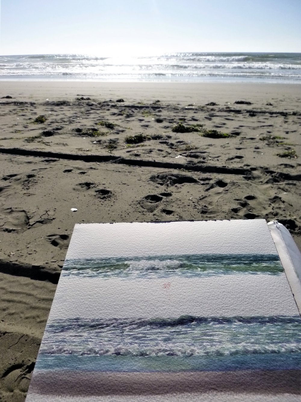 A sketch pad on my lap, on the beach, as I attempt to capture the energy and the light in watercolor...