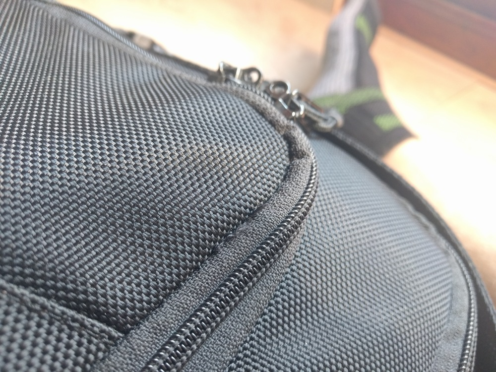 You can see the loose seem and threads emerging just past the curve of the zipper.