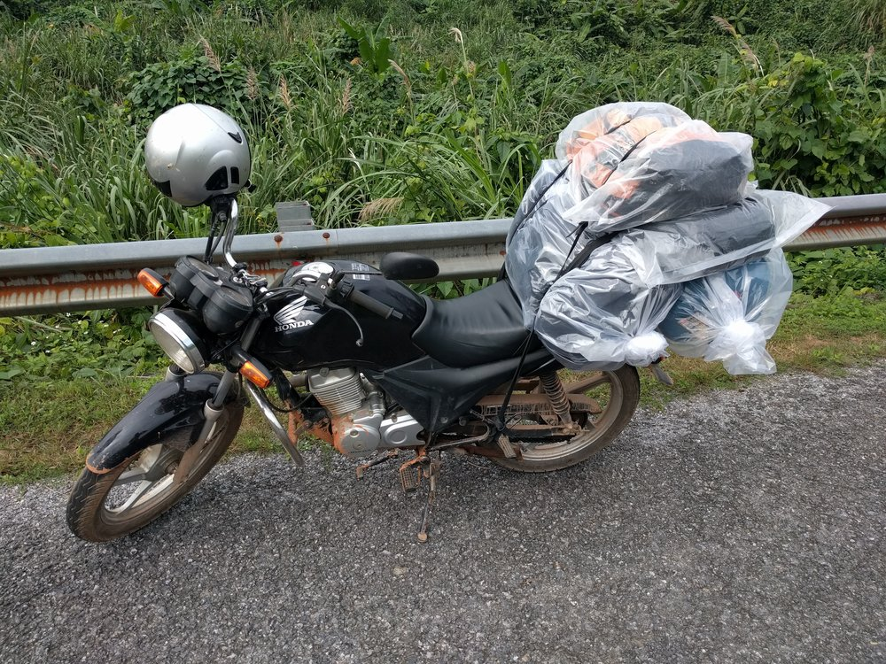 After waterproofing our bags with plastic, Hung strapped our bags and his to the back of his larger Honda Motorcycle.