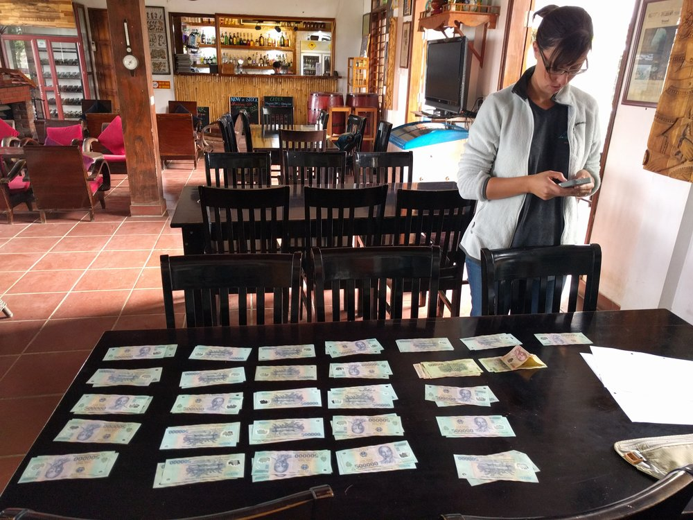 Here's $1200USD in Vietnamese Dong laid out to pay for our two day caving trek in Phong Na. We really loved that experience but increasingly have to ask: is this worth the cost?
