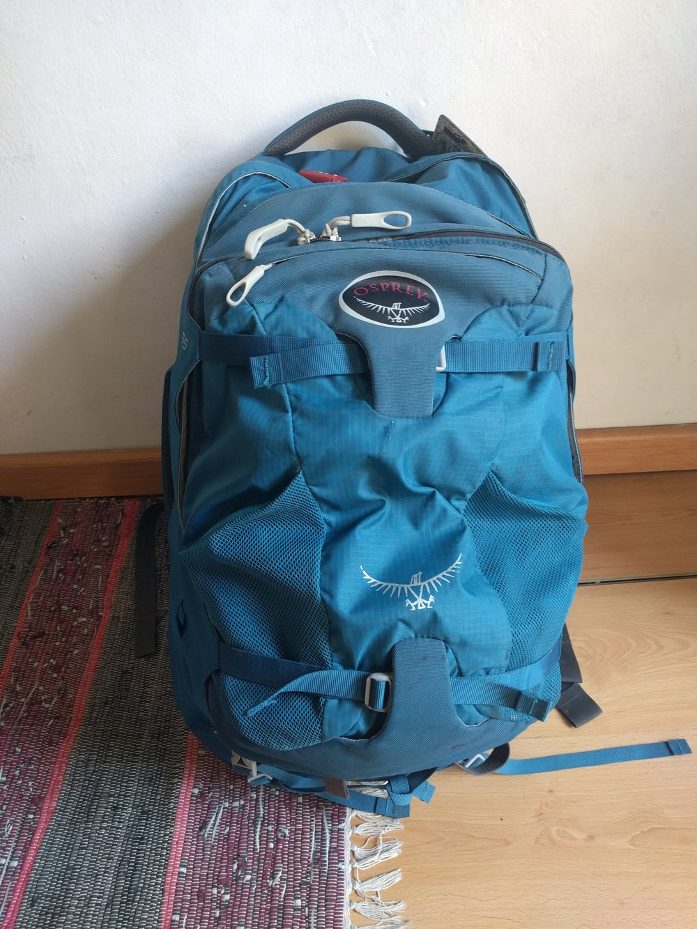 Here you can see the Osprey Farpoint 55 daypack attached to the main bag. The reinforced fabric just under the logo and coming up from the base accommodate retention straps from the main bag that support the main weight of the daypack. It also zips around the rear of the daypack onto the main access panel on the main bag. The connection is very secure, but creates numerous compromises on accessibility and organization in both bags.