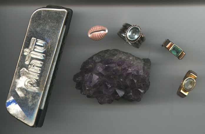"Clockwise from the ghost of Grandpa's harmonica: coffee bean cowry from Emerald Bay, Jimmy Baba's aquamarine, the ""stones of prosperity"" and the Chepren amethyst."
