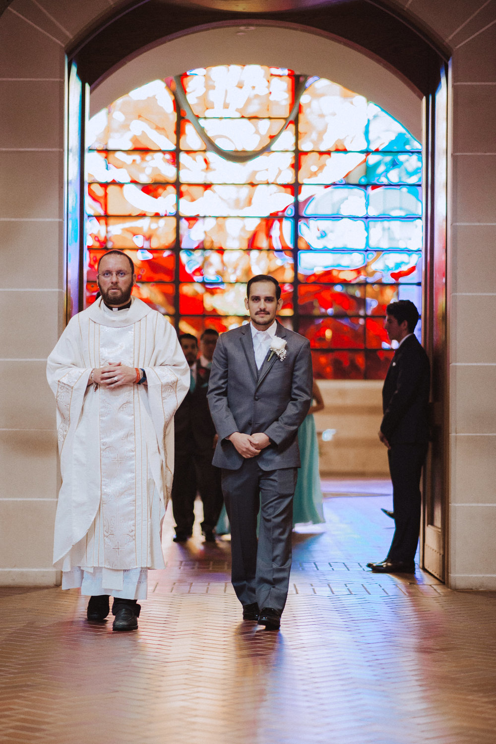 Groom walks down the aisle with Priest