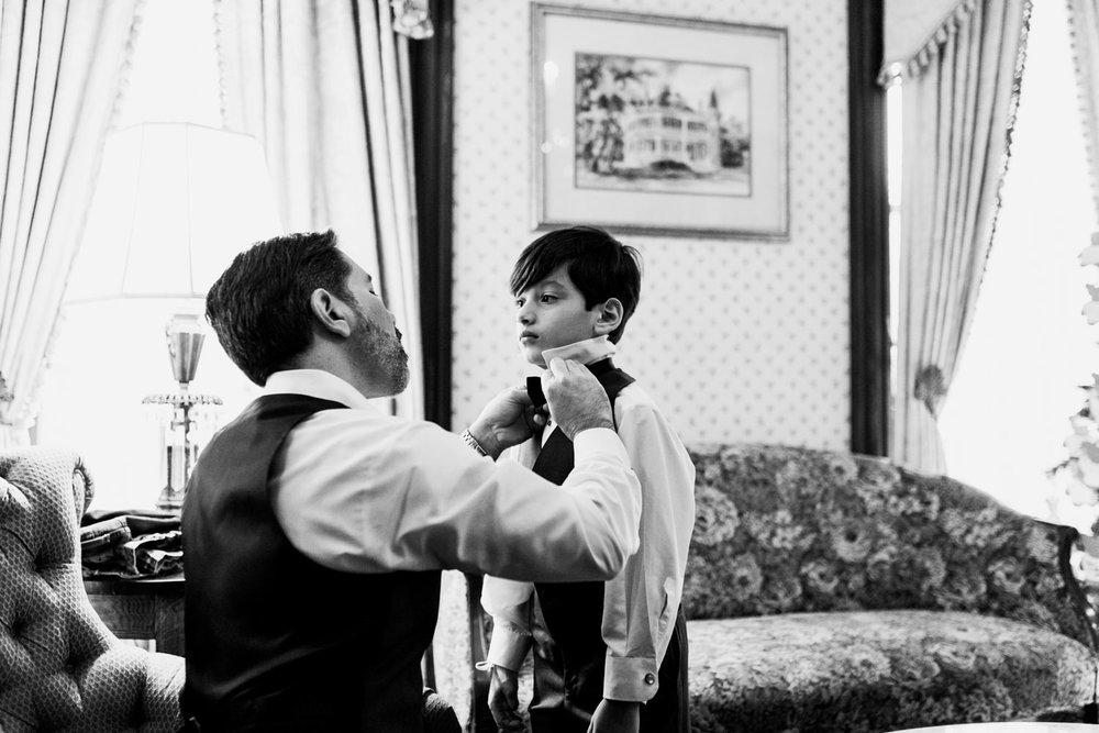 groom putting on boys bow tie at wedding