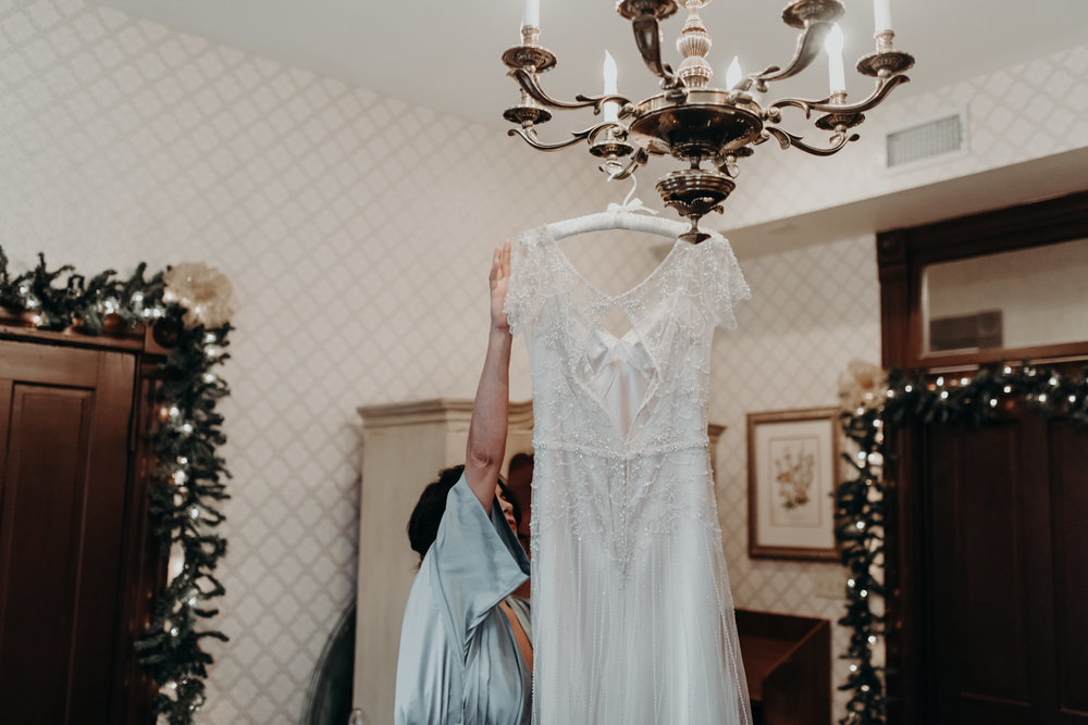wedding dress hanging from chandelier in victorian home
