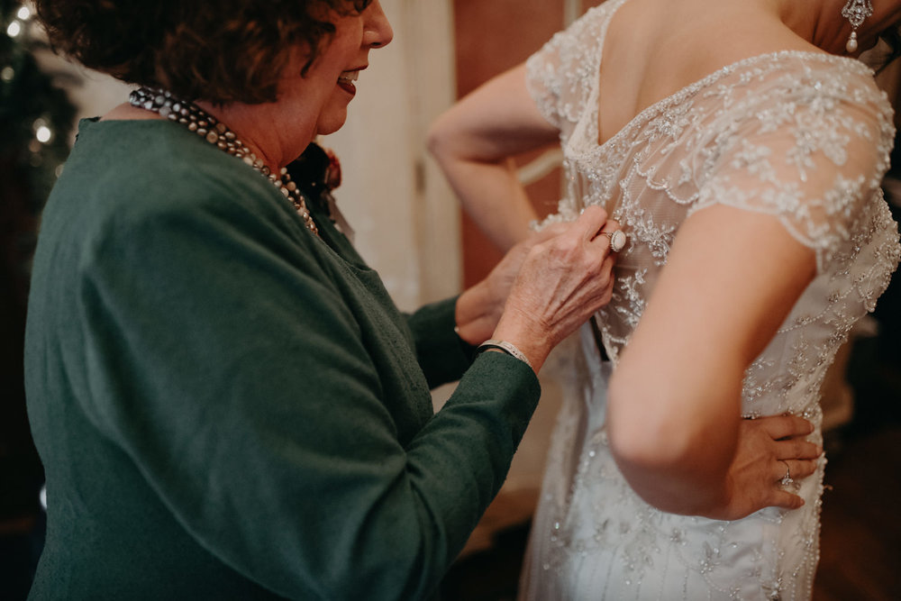 mother of bride buttoning dress
