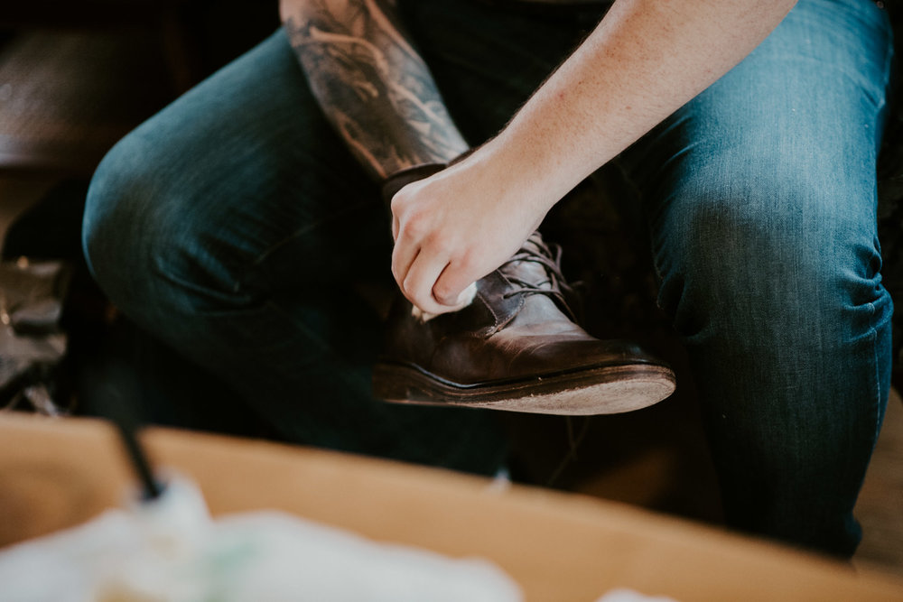 groom polishes shoes for wedding