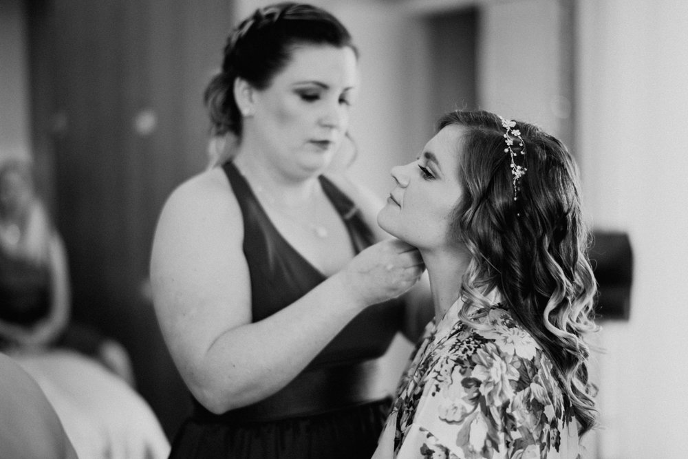 Maid of honor helps bride get ready at Austin wedding