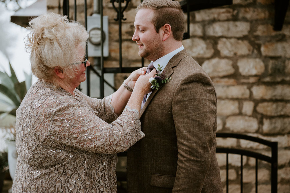 mother helps groom with his tie before austin texas wedding