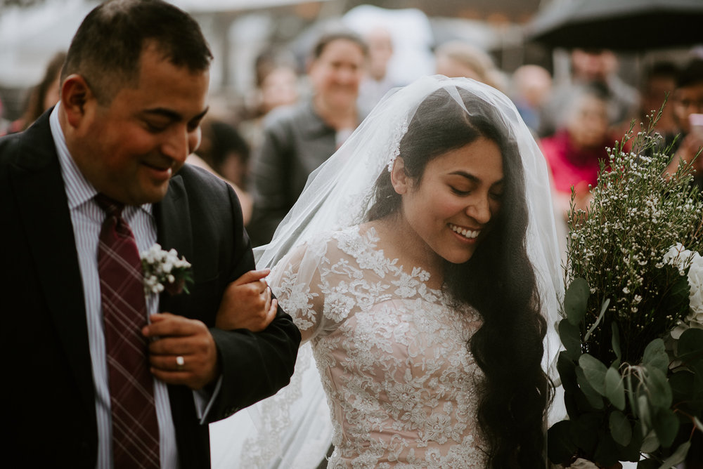 bride walks down the aisle by father