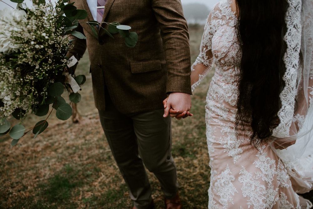 bride and groom hold hands during portraits