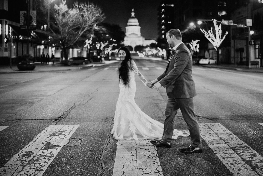 bride and groom cross street in downtown austin