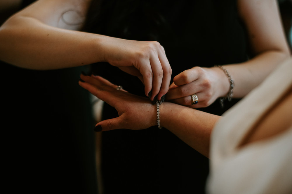 Bride puts on jewelry before houston texas wedding