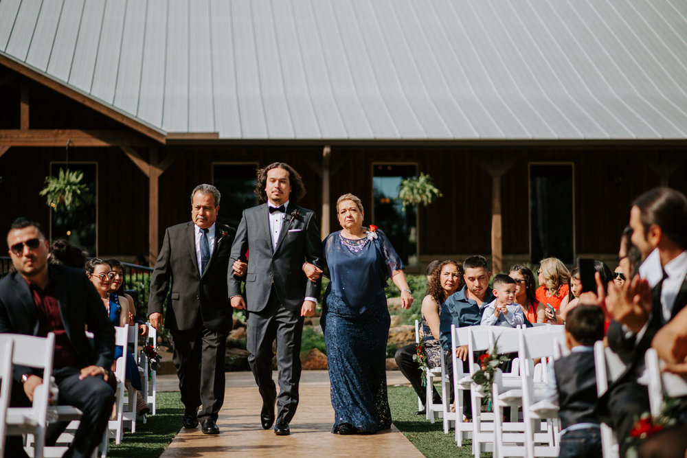 Groom walked down the aisle by parents before houston wedding
