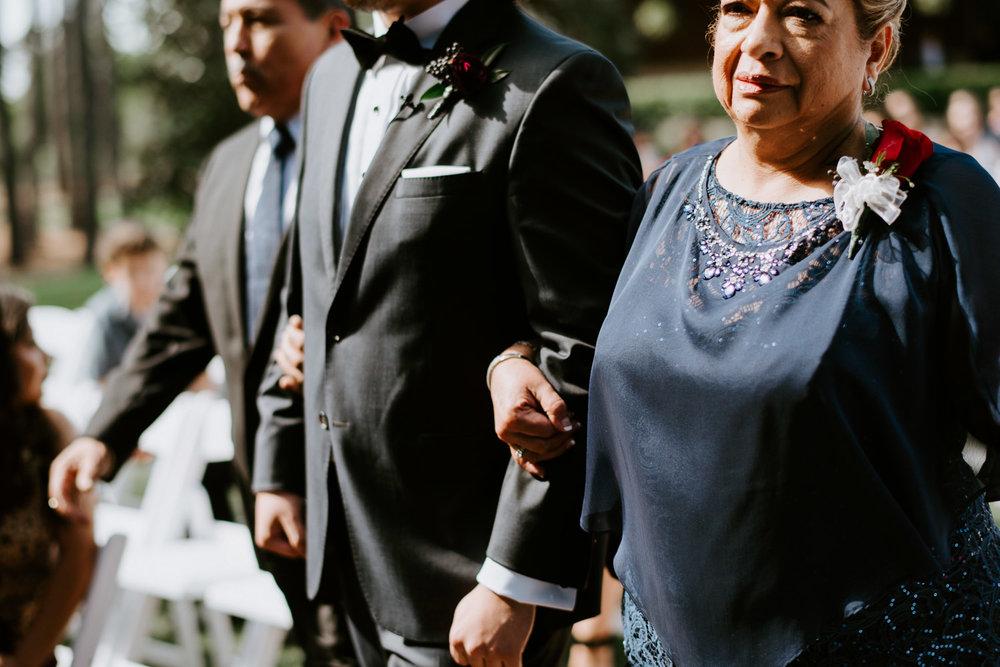 groom walked down the aisle by his parents