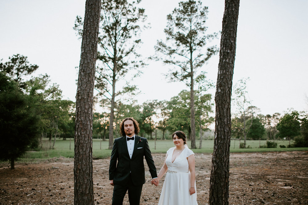 bride and groom pose between trees