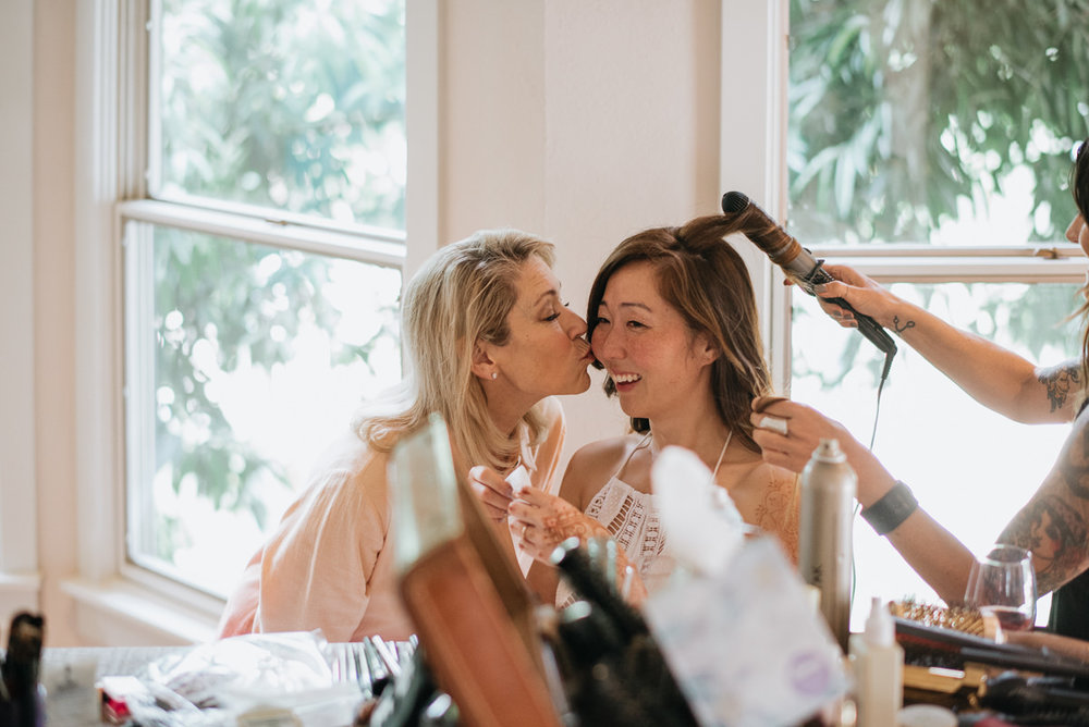 mother gives bride a kiss before wedding
