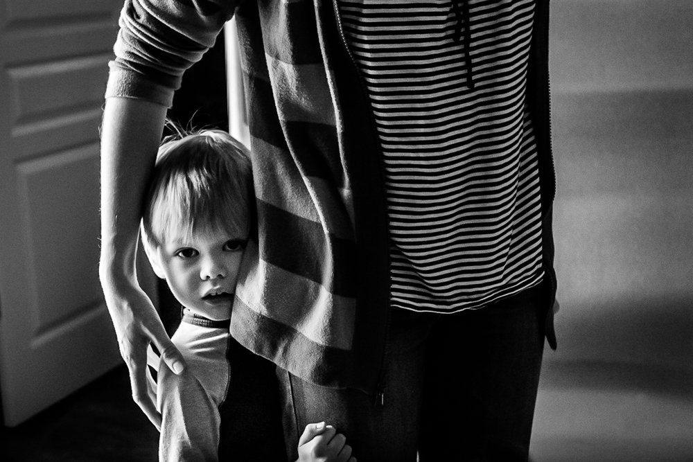 hamilton family photographer dundas family photographer burlington family photographer child photographer candid lifestyle storytelling   black and white image of a little boy half hidden behind his mother's back whos arm is around him protectively