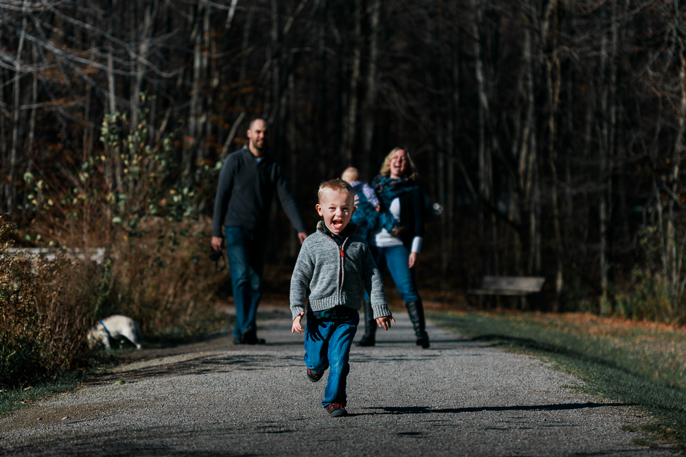 hamilton family photographer dundas family photographer burlington family photographer child photographer candid lifestyle storytelling   A young boy in a sweater and jeans running towards the viewer with mum, dad and baby brother as well as a small dog behind them. Mum and the young boy are laughing