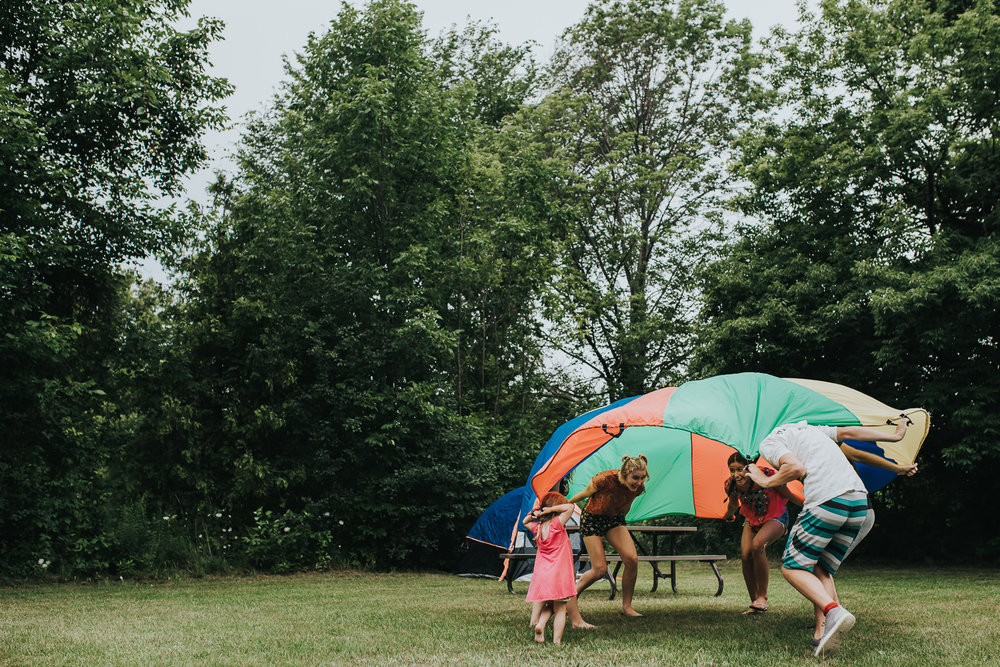 Playing with a colourful parachute at family camp ground outside among the green trees