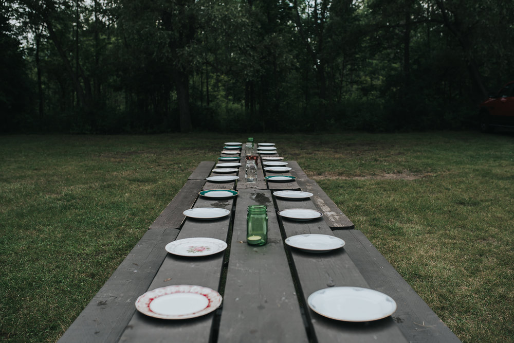 Picnic table set with mix and matched plates and votive candles in mason jars against backdrop of green trees and grass