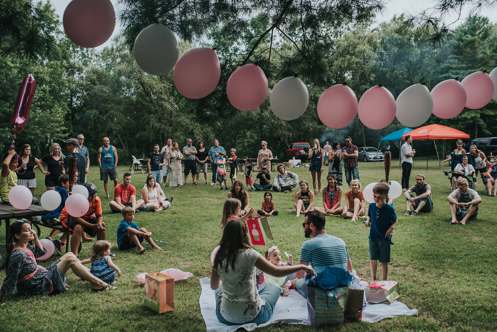 Birthday celebration with pink and white balloons gifts family sitting on a blanket surrounded by family and friends sitting and standing and watching in a camp ground wooded setting