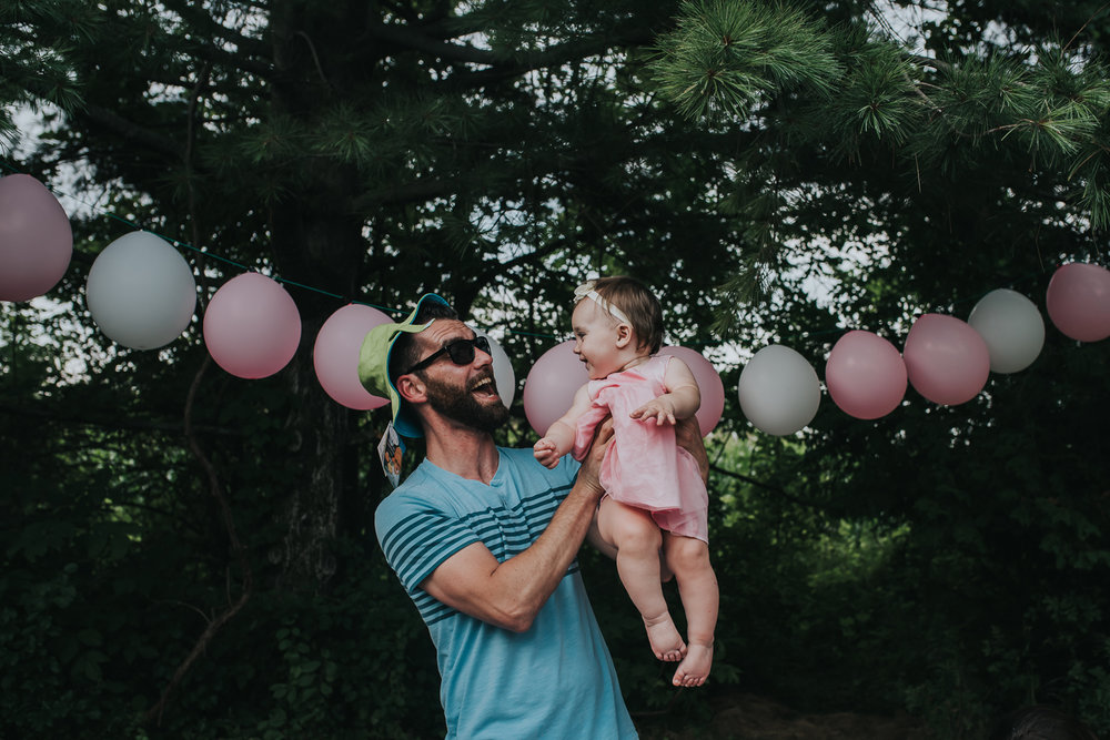 Baby girl dressed in pink being held in the air and smiling at her dad dressed in blue and wearing a green sun hat in front of green trees and a string of pink and white balloons