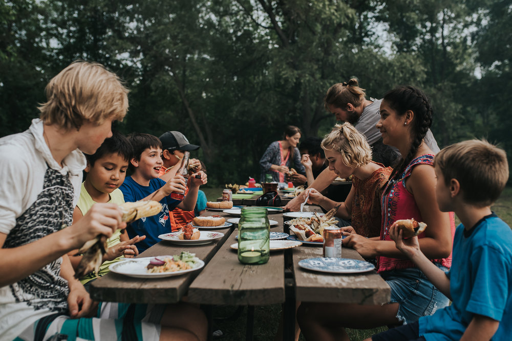 Family and kids eating BBQ meal at long wood picnic table with green trees and wooded back ground