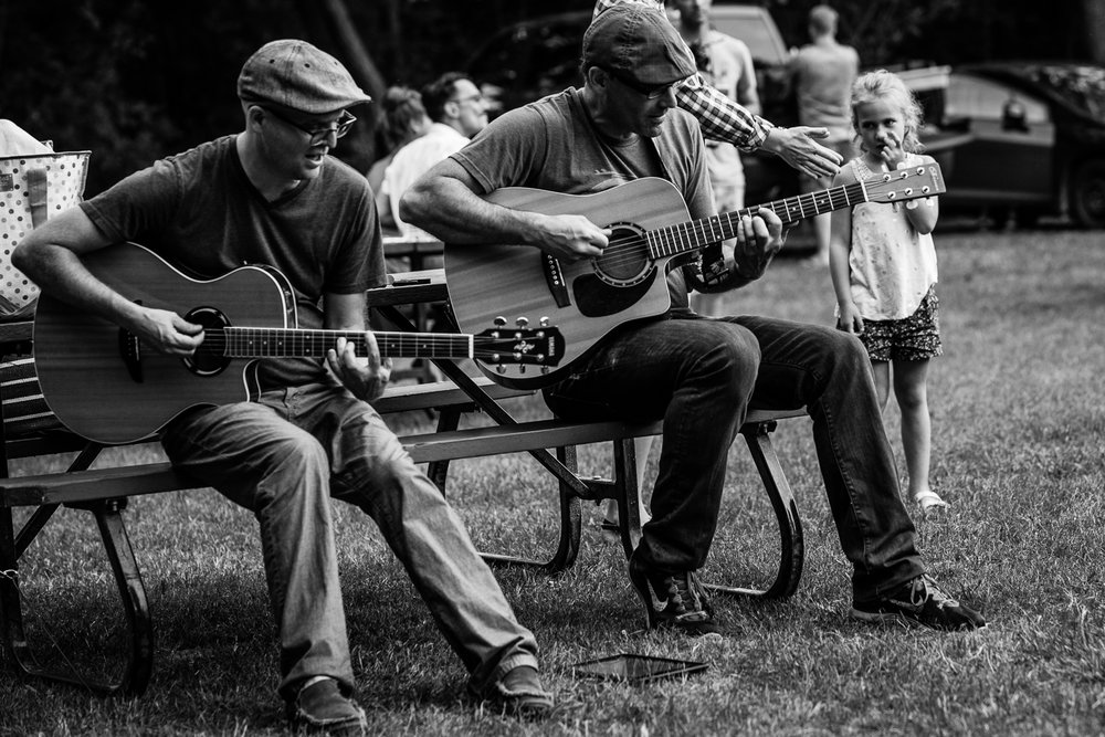 Two men in hats sitting on a picnic table playing acoustic guitars