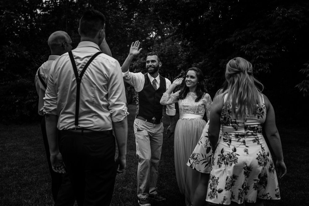 Bride and groom giving high fives to their bridal party