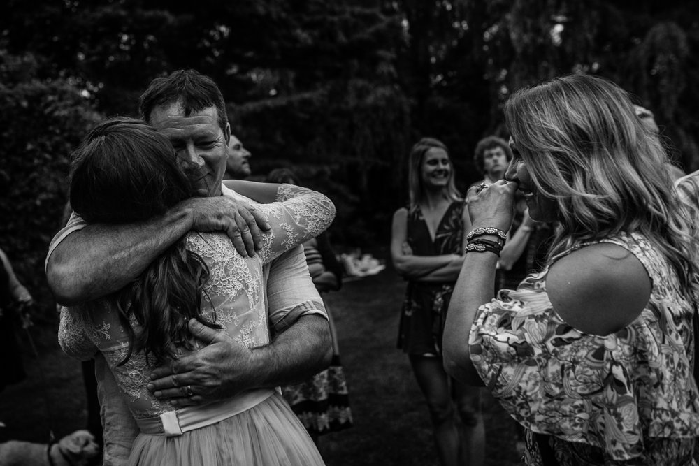 father of the bride hugging the bride as the mother looks on crying
