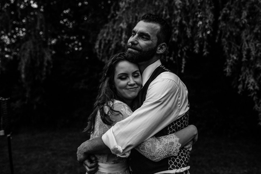 black and white photo of bride and groom hugging one another until the canopy of the trees