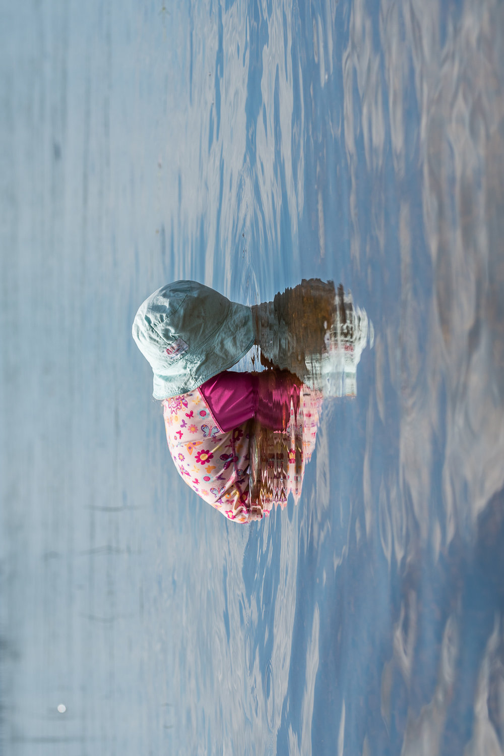 Toddler in a blue sun hat and a pink UV shirt with butterflies and flowers with her face in the blue lake water and her reflection which looks like a heart.