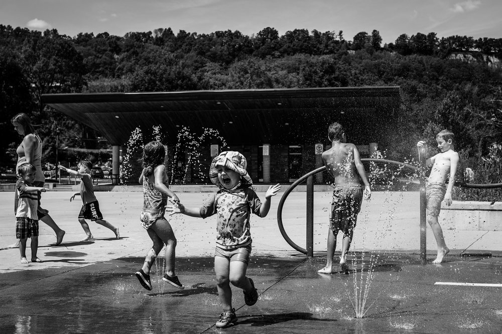 Black and white photograph of six children playing in the splash pad at the Dundas Driving Park in swimsuits and water spraying everywhere