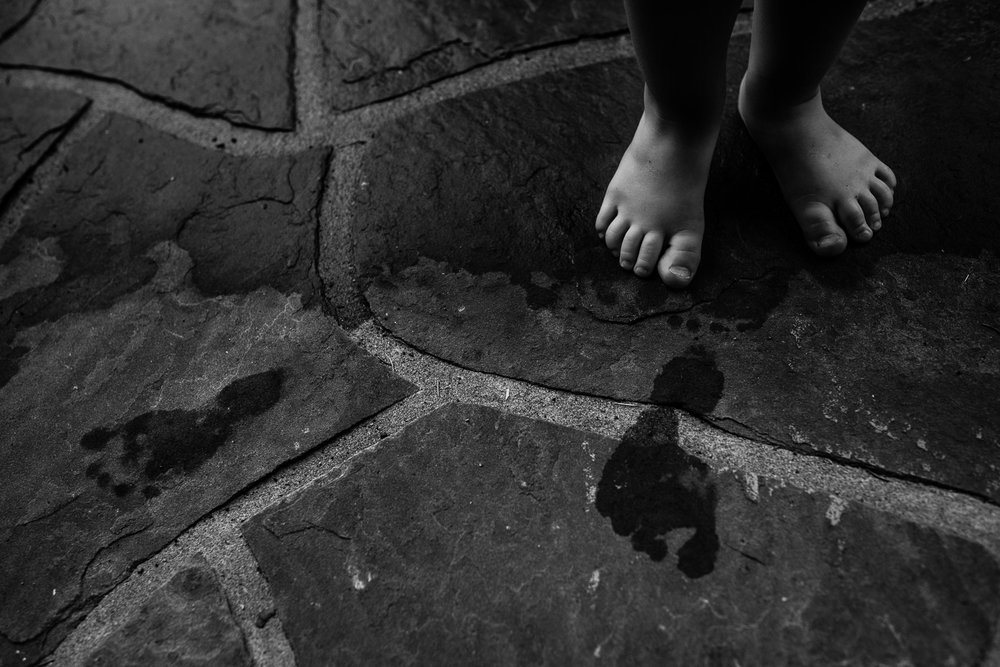 Black and white photo of tiny toddler feet on stone and wet foot prints.