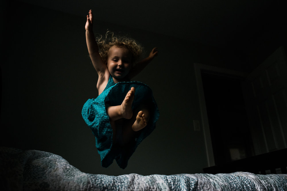 Toddler girl with blond curly hair and a teal blue polkadot dress jumping on the bed with a blue and white floral pattern.
