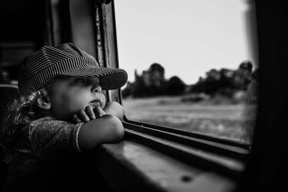 Black and white photograph of a toddler girl in stripped train conductor hat with her chin on folded arms looking out of a window at the trees and landscape with a thoughtful look on her face.