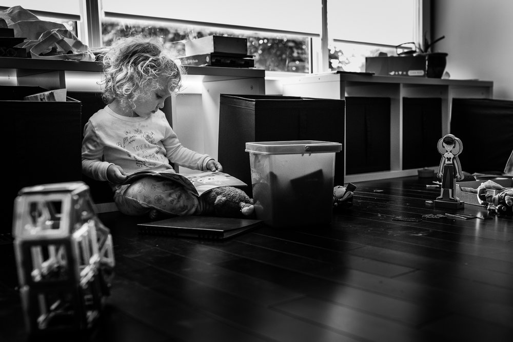 Black and white photograph of a toddler girl with curly hair sitting on the floor surrounded by toys and reading a book