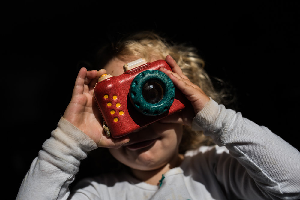 A toddler girl with curly hair holding a red, yellow and green toy camera to her eye