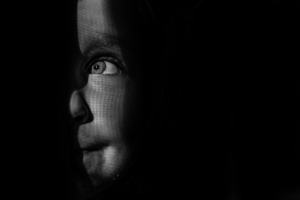 A black and white image of a face in shadow with just one eye and half of a nose and mouth peaking out in the dappled light.