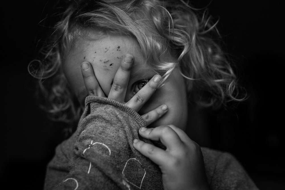 Black and white photo of a toddler girl with curly hair with one eye peaking out from behind her spread fingers on her face which is coming out from the neck hole of her shirt.