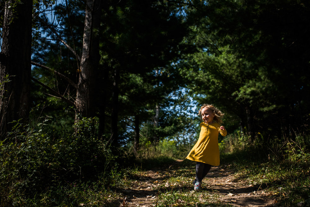 A toddler girl with blond curly hair in a mustard yellow shirt dress, grey leggings and pink and blue sandals skipping down a wooded trail surrounded by green trees