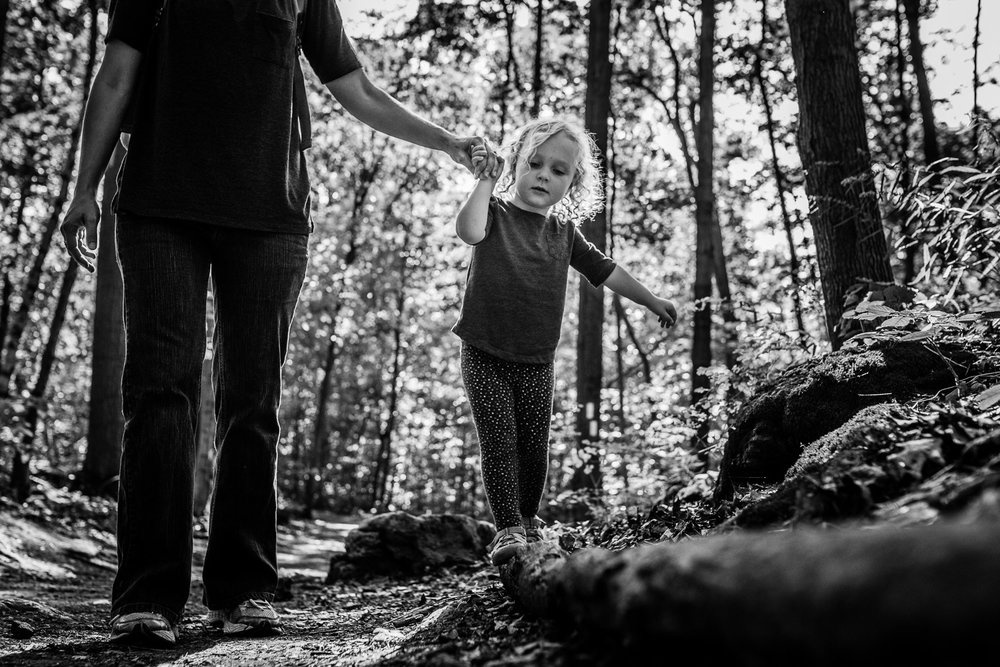 Black and white image of a toddler girl with curly hair holding the hand of her mum as she traverses walking along a fallen tree trunk.